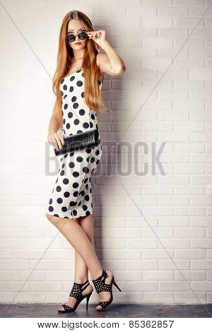 Fashionable lady near white brick wall. Beauty, fashion concept. Optics. Full length portrait.