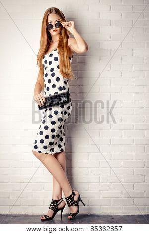 Fashionable lady near white brick wall. Beauty, fashion concept. Optics. Full length portrait.