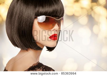 Fashion Brunette Woman In Sunglasses. Black Bob Hairstyle. Red Lips Makeup. Glamour Girl Posing Over
