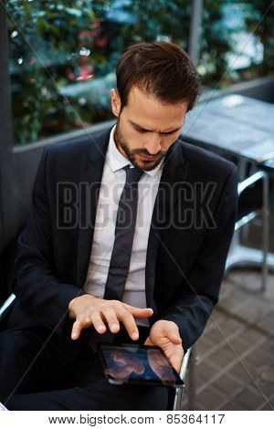 Portrait of young businessman touching digital tablet screen sitting in coffee shop