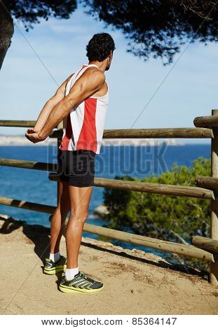 Side shot of handsome young runner stretching his arms before starting run