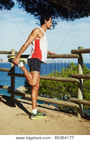 Full length shot of mature man stretching his legs before a run outdoors at sunny day