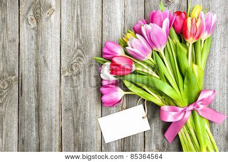 bouquet of spring tulips with empty tag on old wooden background
