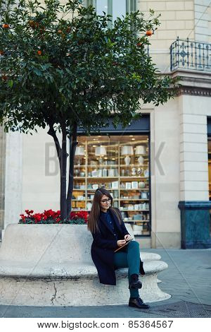 Full length portrait of an attractive young businesswoman sitting outdoors while using her tablet