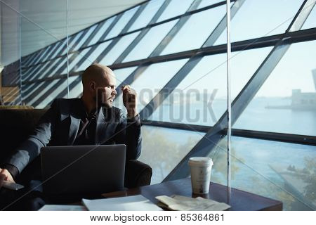 Attractive young business man looking out of airport hall window deep in thought
