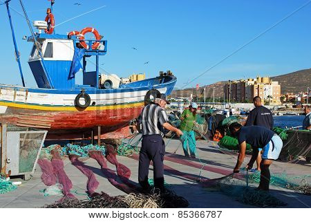 Fishermen tending nets, Spain.