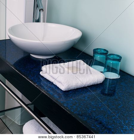 Bathroom sink counter towels water glass blue