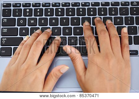 Woman hands typing on laptop keyboard