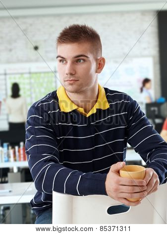 Portrait of young casual caucasian serious office worker with mug, pondering on business,