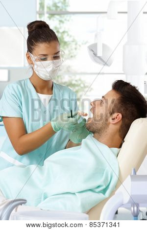 Female dentist trying in denture to young male patient's mouth.