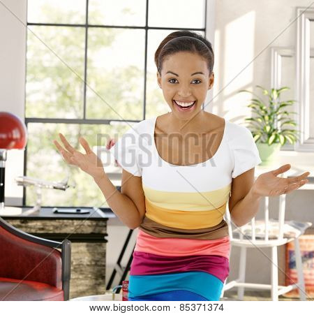 Young afro-american woman laughing happy with arms wide open, looking at camera at home.