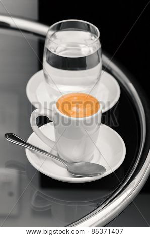 Espresso coffee and glass of water on top table