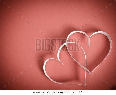 Two Hearts Of White Paper Together Lying On A Red Background