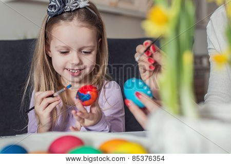 Family, holiday and child concept - close up of little girl and mother coloring eggs for Easter
