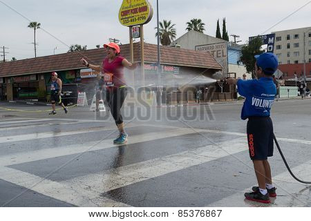 Unidentified Volunteer Boy Throwing Water In A Runner