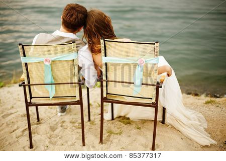 Newlyweds Couple Sitting Near Water On The Beach