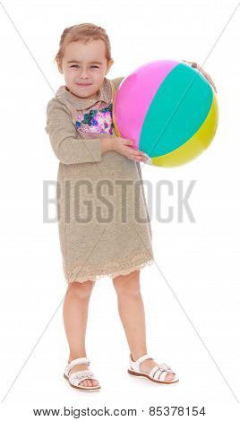 portrait of a little blond-wielding striped inflatable ball