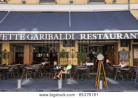 NICE, FRANCE - OCTOBER 2, 2014: People relaxing on patio of Civette Garibaldi restaurant at Place Garibaldi historic square.