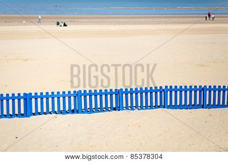 Long Blue Fence On The Beach.
