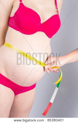 Pregnant Woman With Measuring Tape Around Her Belly