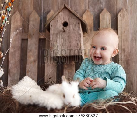 Portrait Of An Adorable Baby Girl And Little White Rabbit