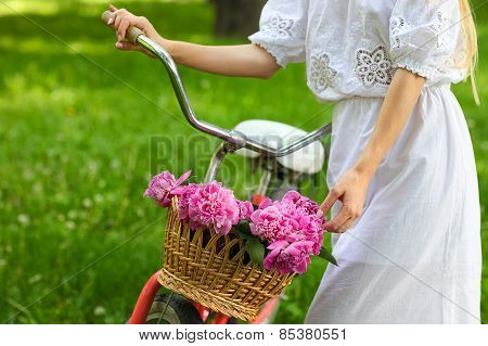 Blond Woman In Park With Bicycle Carrying A Beautiful Basket Of Peony Flowers