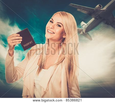 Happy blond woman with passport against blue sky with plane