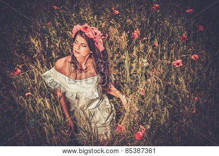 Brunette girl wearing white summer dress and flower chaplet in poppy filed