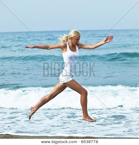Happy Young Woman Jumping In The Beach