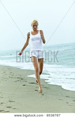 Happy Young Woman Running On The Beach