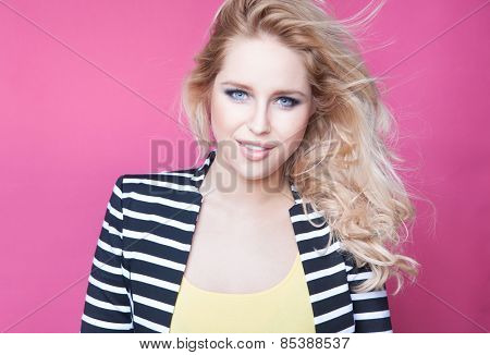 Successful young attractive blonde woman on a pink background