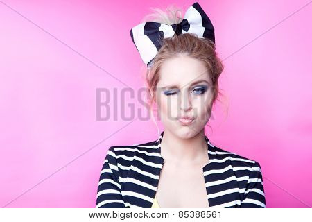 Winking young attractive woman  on pink background