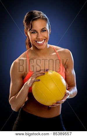 Portrait of young African American woman holding volleyball