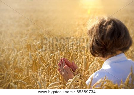 Woman holds wheat and pray
