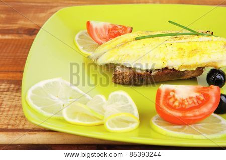 roast fish fillet with tomatoes,chives and bread on plate over wood