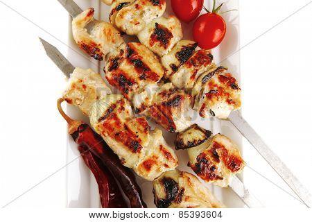 fresh grilled  pork shish kebab on white platter