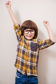 picture of little boys only  - Little boy in eyewear keeping arms raised and smiling while standing against grey background - JPG