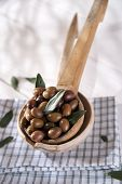 stock photo of ladle  - Presentation of a small group of black olives on wooden ladle  - JPG