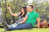 stock photo of two women taking cell phone  - Girl taking a selfie with her boyfriend in a park - JPG