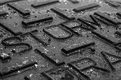 picture of storms  - A close up image of a storm drain lid on the street during a rain storm - JPG