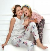 pic of laugh  - Happy mother and four years old daughter laughing together hugging smiling isolated on a white background - JPG