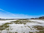 picture of snow clouds  - Wide field in spring with snow and thawed. Already visible green grass. Over a field of bright blue sky with clouds