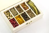 pic of bay leaf  - colorful spices in a wooden box on a white background, turmeric, red pepper, black pepper, cardamom, bay leaf