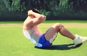 pic of abdominal  - Sport workout and healthy lifestyle concept - fitness man doing abdominal exercises outdoors on the grass ** Note: Visible grain at 100%, best at smaller sizes - JPG