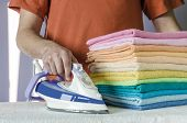 stock photo of belching  - Housework, ironing iron colorful towels on the ironing board. ** Note: Soft Focus at 100%, best at smaller sizes - JPG