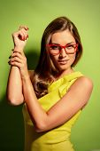 stock photo of spectacles  - Beauty portrait of a positive young woman in spectacles and bright yellow dress over green background - JPG