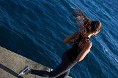 Постер, плакат: Athletic girl jogging over amazing big waves background at sunny day