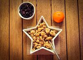 stock photo of roughage  - Healthy granola in a star shaped bowl with a fresh orange and dried fruit - JPG