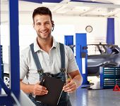 stock photo of auto repair shop  - Happy handsome caucasian male car mechanic at auto repair business shop - JPG