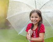 image of rainy weather  - Child with wearing polka dots dress under umbrella in rainy day - JPG
